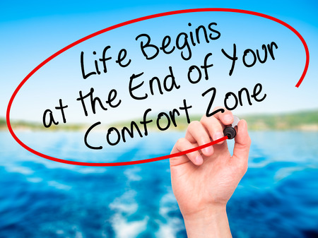 begins: Man Hand writing Life Begins at the End of Your Comfort Zone with black marker on visual screen. Isolated on nature. Business, technology, internet concept. Stock Image