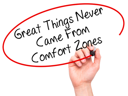 self discovery: Man Hand writing Great Things Never Came From Comfort Zones with black marker on visual screen. Isolated on white. Business, technology, internet concept. Stock Image Stock Photo