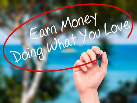 earn money: Man Hand writing Earn Money Doing What You Love with black marker on visual screen. Isolated on nature. Health, technology, internet concept. Stock Image