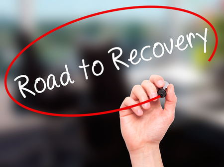 road to recovery: Man Hand writing Road to Recovery with black marker on visual screen. Isolated on office. Business, technology, internet concept. Stock Image
