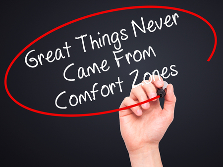 self discovery: Man Hand writing Great Things Never Came From Comfort Zones with black marker on visual screen. Isolated on black. Business, technology, internet concept. Stock Image Stock Photo