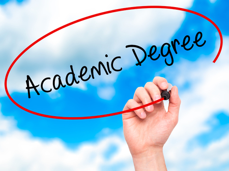 business degree: Man Hand writing Academic Degree with black marker on visual screen. Isolated on sky. Business, technology, internet concept. Stock Photo