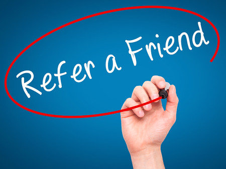 Man Hand writing Refer a Friend  with black marker on visual screen. Isolated on blue. Business, technology, internet concept. Stock Image