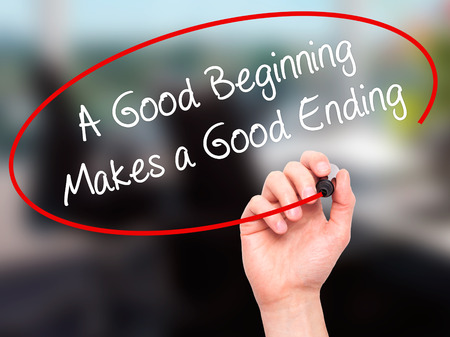 ending: Man Hand writing A Good Beginning Makes a Good Ending with black marker on visual screen. Isolated on office. Business, technology, internet concept. Stock Photo