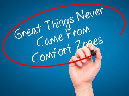 self discovery: Man Hand writing Great Things Never Came From Comfort Zones with black marker on visual screen. Isolated on blue. Business, technology, internet concept. Stock Image