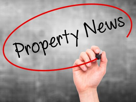 press agent: Man Hand writing Property News with black marker on visual screen. Isolated on grey. Business, technology, internet concept. Stock Image