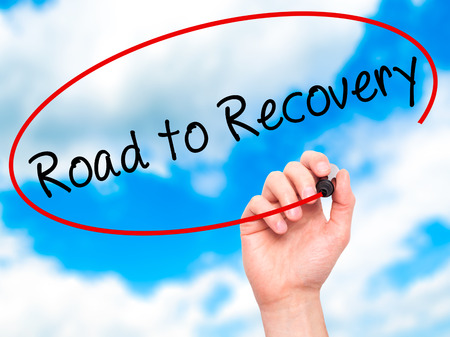 road to recovery: Man Hand writing Road to Recovery with black marker on visual screen. Isolated on sky. Business, technology, internet concept. Stock Image Stock Photo