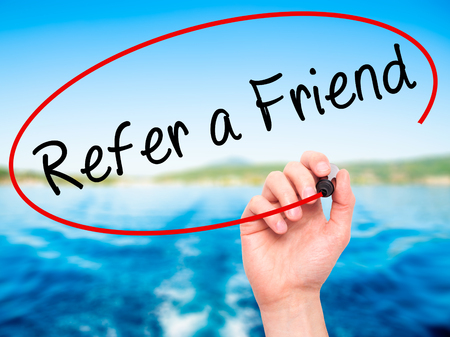 refer: Man Hand writing Refer a Friend  with black marker on visual screen. Isolated on nature. Business, technology, internet concept. Stock Image Stock Photo