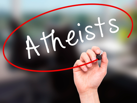 atheism: Man Hand writing Atheists with black marker on visual screen. Isolated on office. Business, technology, internet concept. Stock Image