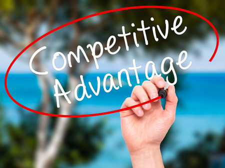 correlate: Man Hand writing Competitive Advantage with black marker on visual screen. Isolated on nature. Business, technology, internet concept. Stock Image