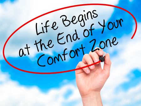 begins: Man Hand writing Life Begins at the End of Your Comfort Zone with black marker on visual screen. Isolated on sky. Business, technology, internet concept. Stock Image