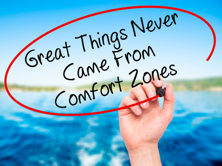 self discovery: Man Hand writing Great Things Never Came From Comfort Zones with black marker on visual screen. Isolated on nature. Business, technology, internet concept. Stock Image