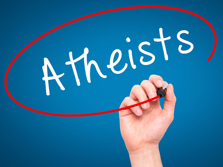 atheist: Man Hand writing Atheists with black marker on visual screen. Isolated on blue. Business, technology, internet concept. Stock Image