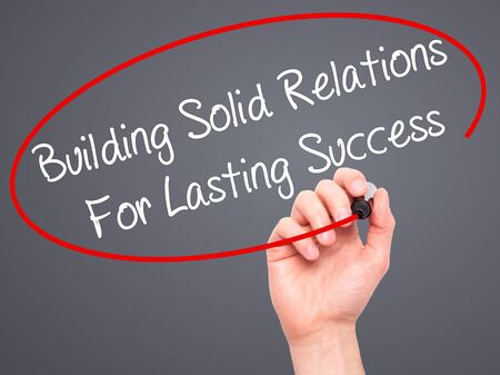 lasting: Man Hand writing Building Solid Relations For Lasting Success with black marker on visual screen. Isolated on grey. Business, technology, internet concept. Stock Image