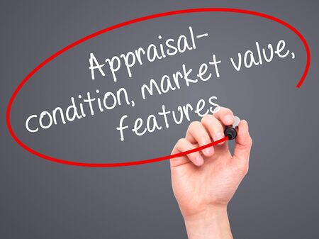 Man Hand writing Appraisal - condition, market value, features, with black marker on visual screen. Isolated on grey. Business, technology, internet concept. Stock Image