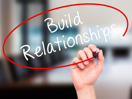Man Hand writing Build Relationships with black marker on visual screen. Isolated on office. Business, technology, internet concept. Stock Image