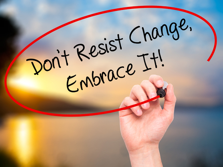 resist: Man Hand writing Dont Resist Change, Embrace It! with black marker on visual screen. Isolated on nature. Business, technology, internet concept.