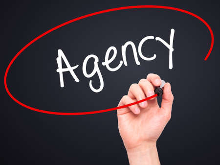 stock agency: Man Hand writing Agency with black marker on visual screen. Isolated on black. Business, technology, internet concept. Stock Photo
