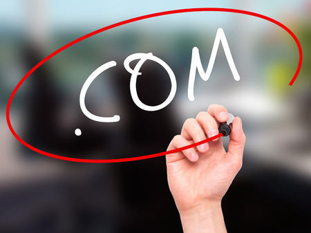suffix: Man Hand writing .COM with black marker on visual screen. Isolated on office. Business, technology, internet concept. Stock Image