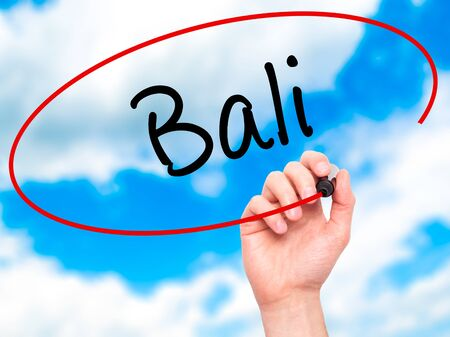 bali province: Man Hand writing Bali  with black marker on visual screen. Isolated on sky. Business, technology, internet concept. Stock Photo Stock Photo