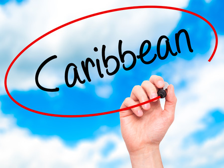 port au prince: Man Hand writing Caribbean  with black marker on visual screen. Isolated on sky. Business, technology, internet concept. Stock Photo Stock Photo