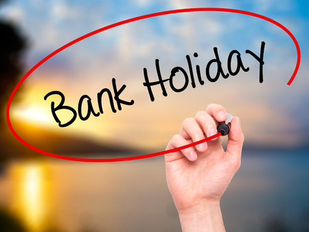 Man Hand writing Bank Holiday with black marker on visual screen. Isolated on background. Business, technology, internet concept. Stock Photo 스톡 콘텐츠