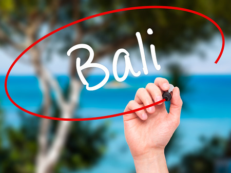 bali province: Man Hand writing Bali  with black marker on visual screen. Isolated on nature. Business, technology, internet concept. Stock Photo Stock Photo