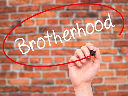 fraternidad: Hombre de la mano escribiendo Hermandad con marcador negro en la pantalla visual. Aislado en el fondo. Negocios, la tecnología, el concepto de internet. Foto de stock Foto de archivo
