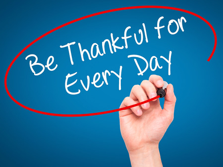 Man Hand writing Be Thankful for Every Day   with black marker on visual screen. Isolated on blue. Business, technology, internet concept. Stock Photo