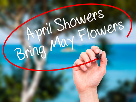 april: Man Hand writing April Showers Bring May Flowers with black marker on visual screen. Isolated on nature. Business, technology, internet concept. Stock Photo Stock Photo