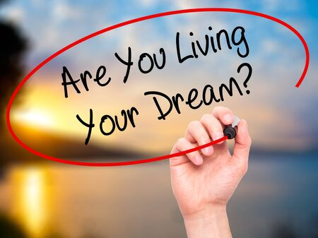living wisdom: Man Hand writing Are You Living Your Dream? with black marker on visual screen. Isolated on nature. Business, technology, internet concept. Stock Photo