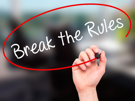 rebelling: Man Hand writing Break the Rules with black marker on visual screen. Isolated on office. Business, technology, internet concept. Stock Photo