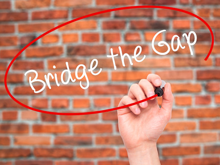 bridging the gaps: Man Hand writing Bridge the Gap with black marker on visual screen. Isolated on bricks. Business, technology, internet concept. Stock Photo Stock Photo