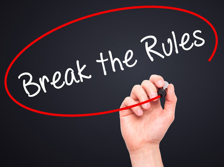 libertarian: Man Hand writing Break the Rules with black marker on visual screen. Isolated on black. Business, technology, internet concept. Stock Photo Stock Photo