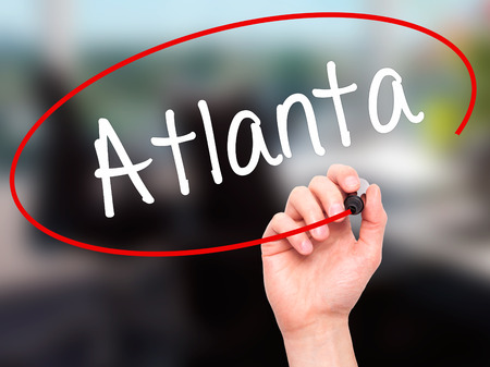 atlanta tourism: Man Hand writing Atlanta with black marker on visual screen. Isolated on background. Business, technology, internet concept. Stock Photo