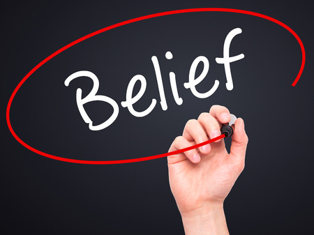 Man Hand writing Belief with black marker on visual screen. Isolated on black. Business, technology, internet concept. Stock Photo