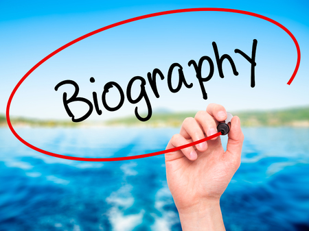 Man Hand writing Biography  with black marker on visual screen. Isolated on nature. Business, technology, internet concept. Stock Photo Standard-Bild