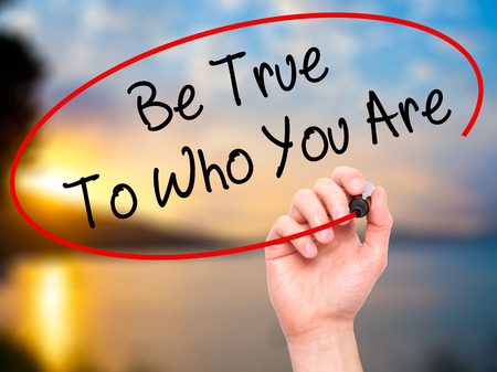 individualism: Man Hand writing Be True To Who You Are with black marker on visual screen. Isolated on nature. Business, technology, internet concept. Stock Photo