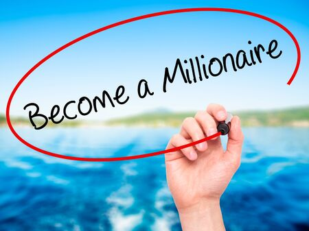 hombre millonario: Man Hand writing Become a Millionaire with black marker on visual screen. Isolated on nature. Business, technology, internet concept. Stock Photo