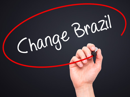 protestors: Man Hand writing Change Brazil  with black marker on visual screen. Isolated on black. Business, technology, internet concept. Stock Photo Stock Photo