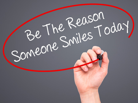 someone: Man Hand writing Be The Reason Someone Smiles Today  with black marker on visual screen. Isolated on grey. Business, technology, internet concept. Stock Photo Stock Photo