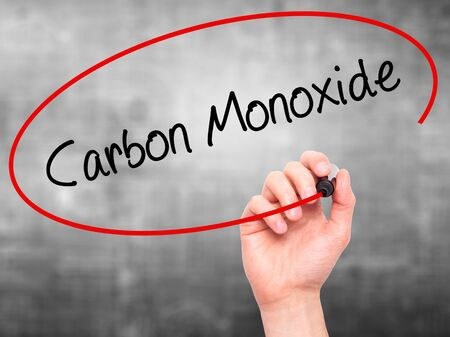 noxious: Man Hand writing Carbon Monoxide  with black marker on visual screen. Isolated on grey. Business, technology, internet concept. Stock Photo