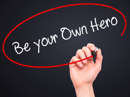 father in law: Man Hand writing  Be your Own Hero  with black marker on visual screen. Isolated on black. Business, technology, internet concept. Stock Photo Stock Photo