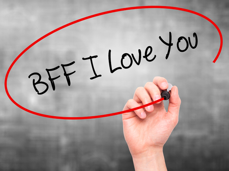 nota: Man Hand writing BFF I Love You with black marker on visual screen. Isolated on grey. Business, technology, internet concept.