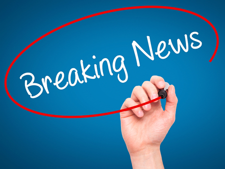 annoucement: Man Hand writing Breaking News with black marker on visual screen. Isolated on blue. Business, technology, internet concept. Stock Photo