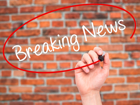 annoucement: Man Hand writing Breaking News with black marker on visual screen. Isolated on bricks. Business, technology, internet concept. Stock Photo