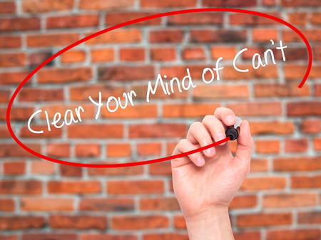 cant: Man Hand writing Clear Your Mind of Cant with black marker on visual screen. Isolated on bricks. Business, technology, internet concept. Stock Photo Stock Photo