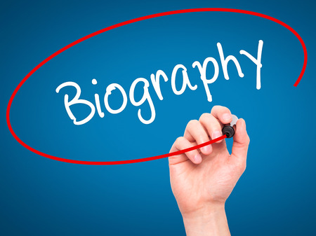 memoir: Man Hand writing Biography  with black marker on visual screen. Isolated on blue. Business, technology, internet concept. Stock Photo
