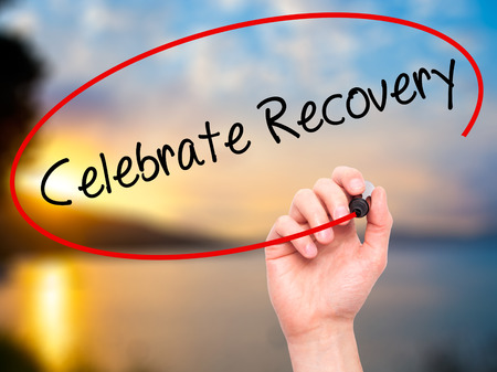 recovery: Man Hand writing Celebrate Recovery with black marker on visual screen. Isolated on nature. Business, technology, internet concept. Stock Photo