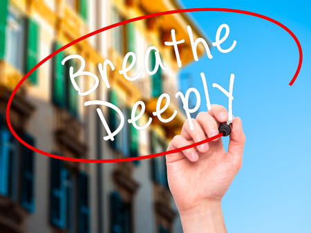 deeply: Man Hand writing Breathe Deeply with black marker on visual screen. Isolated on city. Business, technology, internet concept. Stock Photo